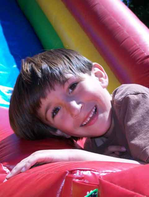Happy boy on an inflatable slide at Pettit Creek Farms